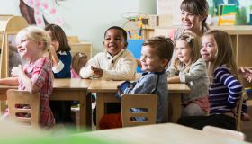 Teacher with group of preschoolers sitting at table