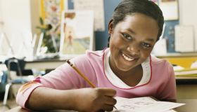 Portrait of a Schoolgirl Writing in Her Exercise Book in a Classroom