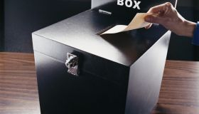 Man Inserting Voting Paper into a Ballot Box