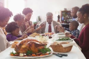 Family saying grace at holiday table