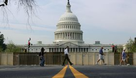 Pedestrians walk past the US Capitol and
