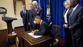 US President Barack Obama (C) signs a di