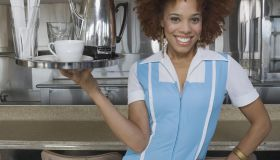 Waitress carrying tray of coffee and cup