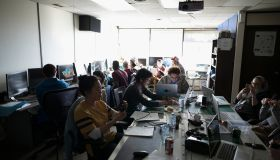 Hackers working hackathon at laptops and computers in dark office
