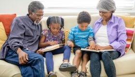 Grandparents sitting on sofa with two grandchildren, reading