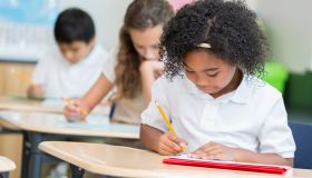 Confident African American private school student takes test in class