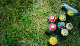 High Angle View Of Colorful Spray Paints On Grassy Field