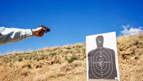 Shooting handgun at human silhouette target.