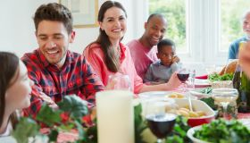 Portrait smiling woman enjoying Christmas dinner with family at table