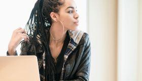 Black teenage girl looking away from laptop