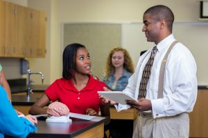African American high school science teacher works with students