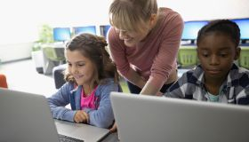 Female teacher and pre-adolescent girls using laptops in classroom