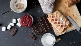 Overhead view of apple strudel, chocolate, cake and ingredients on kitchen table