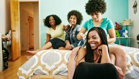 Woman braiding hair of friend in bedroom