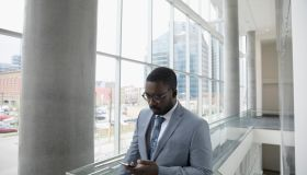 Businessman texting with cell phone in office