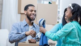 Young family of three packs clothes in moving box together