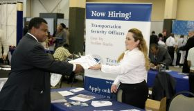 A woman handing a brochure to a man at the Transportation Security Administration booth at a job fair in Miami