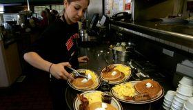 Gaby Estrella (Cq), prepares a tray of Grand Slam breakfast at Denny's Restaurant in Santa Ana on t