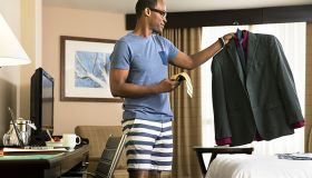 Black man in hotel room matching tie and suit on coathanger