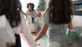 Daughters surprising mother with Christmas gifts in living room
