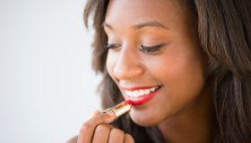 Black woman applying lipstick