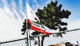 California Flag On Fence Against Cloudy Sky