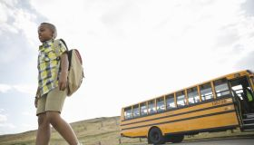 Low angle view of schoolboy walking away from school bus