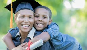 Tween son poses with mom after her college graduation ceremony