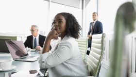 Confident, attentive businesswoman listening in conference room meeting