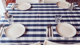 White plates, fork and knives, blue stripy tablecloth, drinking glasses