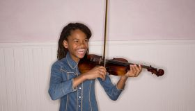 Girl (10-11) playing violin, laughing