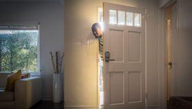 Father arriving home peeping through open front door
