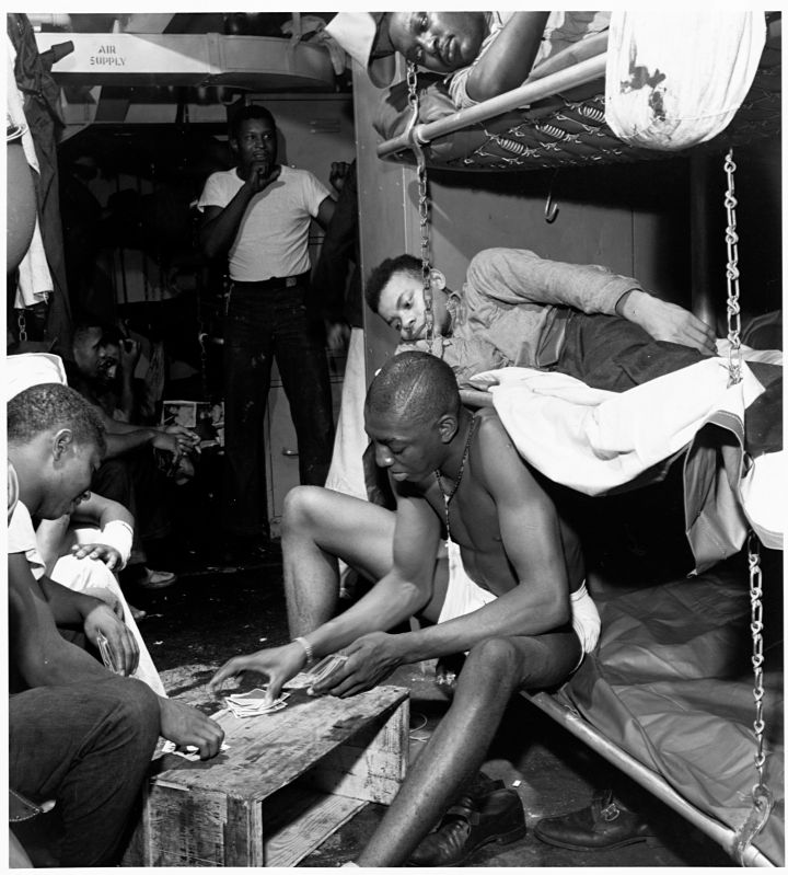 Stewards mates passing time the evening before battle at Manila with a card game in their bunk room. November, 1944.