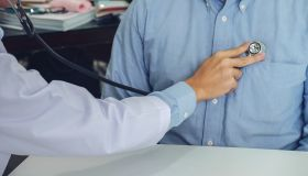 Midsection Of Doctor Examining Patient At Hospital
