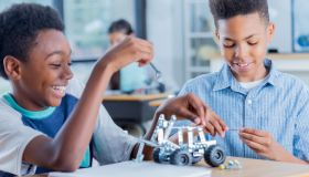 Two preteen boys work on robotics project together at school