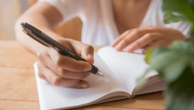 Hands of African American woman writing in journal