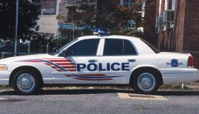 USA, Washington DC, police car parked outside police station next to stars-and-stripes flag on a mast, side view