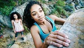 Woman watching friend rock climbing