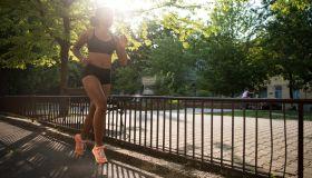 Fitness woman jogging outside under sun