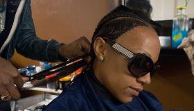 A lady braiding a customers hair
