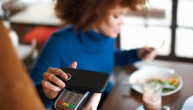 Customer in cafe making contactless payment with mobile phone