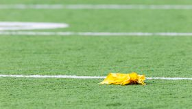 Penalty flag laying on American football field
