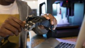 Close up male designer examining robotic hand prototype at laptop next to 3D printer