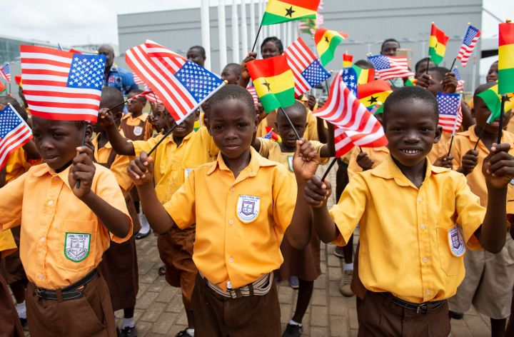 Children wave the American and Ghana flags