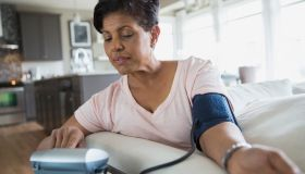 Woman checking blood pressure in living room