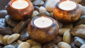 Close-up of lit tea light candles in dish of stones