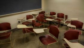 Empty chairs and desks randomly placed in a college classroom.