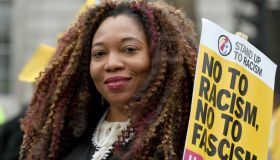 A protester seen holding a placard that says no to racism,...