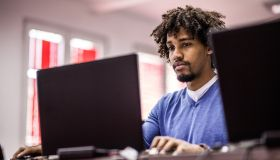 African American student studying on laptop at computer lab.