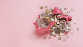 Broken piggybank on a pink surface.